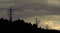 High voltage electricity pylons on hill, overcast,sunset sky, clouds Stock Footage