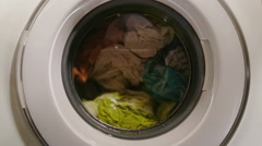 Wet clothes turning in washing machine, view through front glass Stock Footage