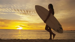Surfer woman in silhouette walking with surfboard at sunset on tropical beach Stock Footage