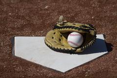 Baseball Catchers Mitt On Homeplate With White Baseball - stock photo