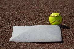 Fair Ball Yellow Fastpitch Softball Hits Base - stock photo