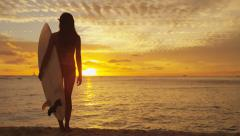 Young female surfer standing on beach sand sunset holding surfboard Stock Footage