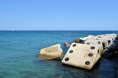 Coastline with concrete wave breaker in the shape of dice - stock photo