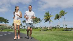 Sport couple exercising running outside on street in summer Stock Footage