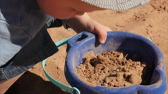 Adorable little boy filling bucket with sand on beach Stock Footage