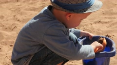 A cute boy filling bucket with sand on beach Stock Footage