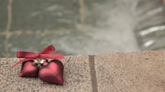 Hearts lie by the pool on a granite stone. Stock Footage