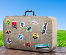 old travel suitcase on background with grass field - stock photo
