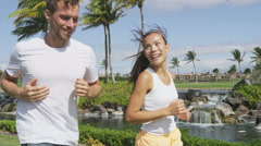 Running couple of runners jogging together in park - Active summer lifestyle Stock Footage