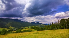 4K UHD. Time-lapse of stormy clouds passing by green summer fields with dark Arkistovideo