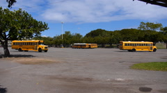 School buses arriving to baseball stadium Stock Footage