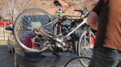 Man strapping a bike on the bike rack Stock Footage