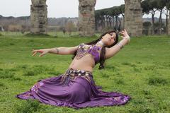 purple belly dancer under the Roman aqueduct - stock photo