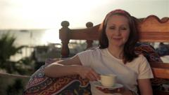 Young girl woman relaxing in cafe street veranda, drinking coffee enjoying life Stock Footage