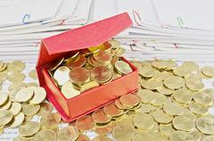 Gold coins overload from red box Stock Photos
