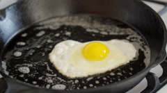 Cook flips fried egg over in a cast iron pan 4K Stock Footage