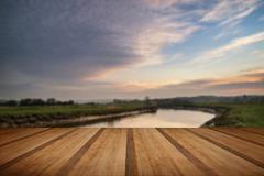 Stunning vibrant sunrise reflected in calm river  with wooden planks floor - stock illustration