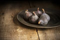 Fresh figs in moody natural lighting set with vintage retro style Stock Photos