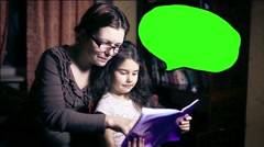 Mom and daughter woman and child reading book at home tonight place for your Stock Footage
