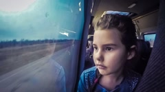 Teen girl child rides in the car looking out the window the road shaking video - stock footage
