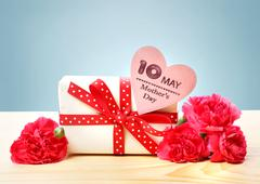 Mothers Day May 10th message with present and carnations Stock Photos