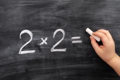 Child solving math problem on the blackboard Stock Photos