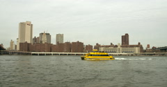 Water taxi on the East River passing beneath the Brooklyn Bridge Stock Footage