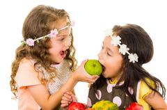 Beautiful healthy little girls eating delicious fresh fruits Stock Photos