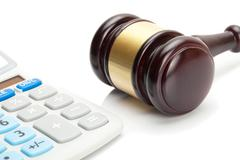 Wooden judge's gavel and calculator Stock Photos