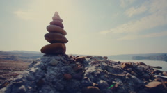 Abstract background. Stone tower on a pebble beach again blue sky Stock Footage