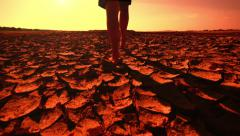 Global warming concept. Young woman walking across desert Stock Footage
