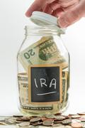 Hand opening glass Jar used for IRA fund - stock photo