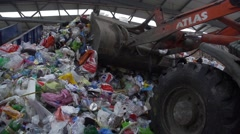Bulldozer scoops up a pile of plastic waste in recycling factory Stock Footage