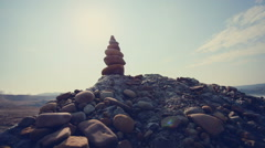 DOLLY MOTION: Stones pyramid on sand symbolizing zen, harmony, balance - stock footage