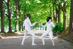 Two rapier fencers women staying in park alley getting ready for competition - stock photo