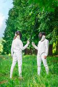 Two fencers women staying in park with crossed rapiers Stock Photos