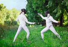 Two rapier fencer women fighting over beautiful nature background Stock Photos