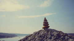 DOLLY MOTION: Pyramid of stones on a background of solar hot landscape with Stock Footage