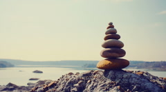 Pyramid of stones on a sand hill Stock Footage