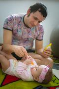 Papa feeds child with spoon. Image of young dad - stock photo