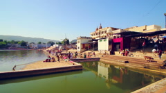 People and cows gather at the ghats of Pushkar Lake, India - stock footage