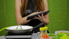 Female cook with tablet computer while cooking Stock Footage