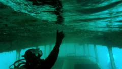 In Double Decker Bus wreck a scuba diver plays with bubbles - stock footage