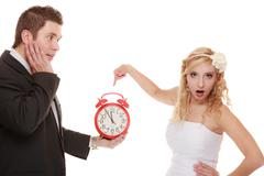 Wedding. Time to get married. Bride groom with clock. - stock photo