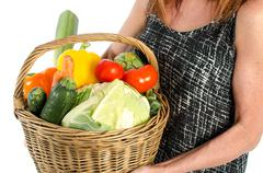 Woman holding a basket full of vegetables Stock Photos