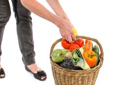 Woman with a basket full of vegetables Stock Photos