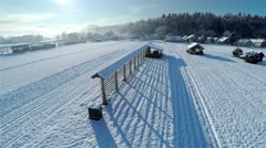 Ascending over farm covered in snow on a sunny day 4K Stock Footage