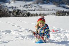 little 3 year old child playing in the snow - stock photo