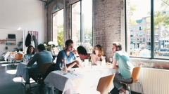 Many Young People in Bright Stylish Restaurant - stock footage