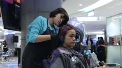 Hair stylist applying hair coloring dye to lighten up the hair tone -Dan - stock footage